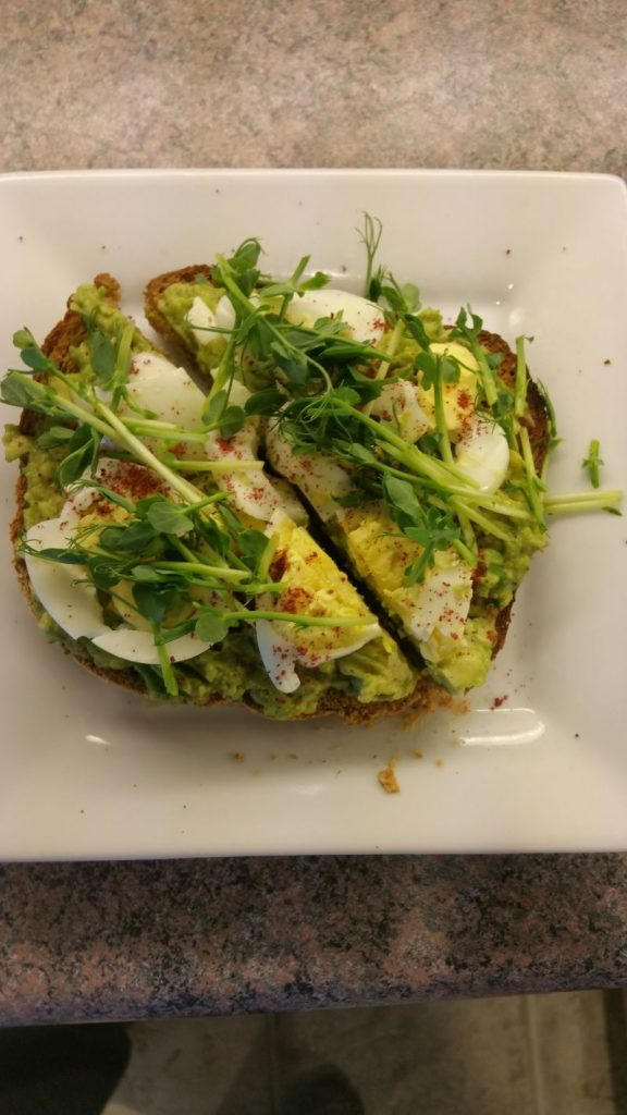 A tasty sandwich with eggs covered with microgreens